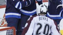 Winnipeg Jets' Eric Tangradi (27), Blake Wheeler (26) and Keaton Ellerby (7) celebrate Tangradi's goal against Colorado Avalanche's goaltender Reto Berra (20) during first period NHL action in Winnipeg on Wednesday, March 19, 2014. (JOHN WOODS/THE CANADIAN PRESS)