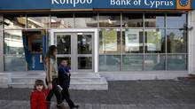 A woman with children walks past a branch of Bank of Cyprus at Glyfada suburb in Athens March 17, 2013. Athens has started exploring local lenders' interest in taking over the Greek units of Cypriot banks, as part of the island's international bailout agreed earlier on Saturday, Greece's finance minister said. (YORGOS KARAHALIS/REUTERS)