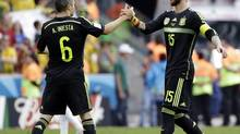 Spain's Andres Iniesta and Sergio Ramos greet at the end of the group B World Cup soccer match between Australia and Spain at the Arena da Baixada in Curitiba, Brazil, Monday, June 23, 2014. (Fernando Vergara/AP)