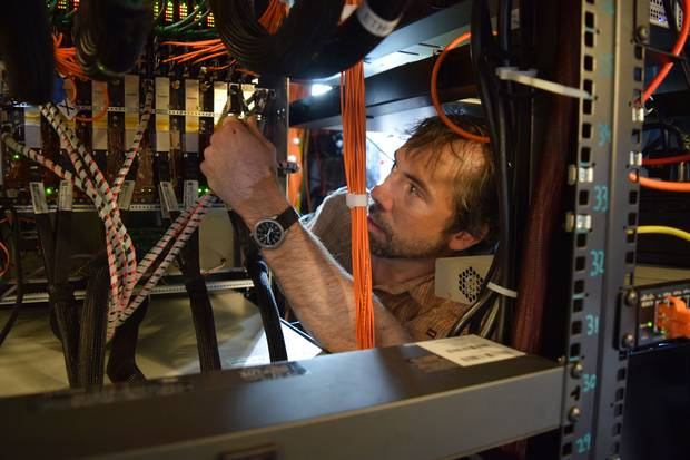Matt Dobbs, an astrophysicist at McGill University and member of the CHIME team, works on the guts of the electronics used to process data from the experiment.