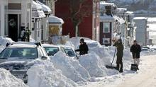 St. John's residents take a break from shovelling after a snowstorm hit the city Jan. 5. Extreme wind-chill values in some parts of the country have prompted fears of frostbite that can strike just in five to 10 minutes. (Paul Daly/CP)