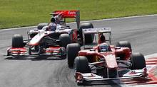 McLaren Formula One driver Jenson Button of Britain is overtaken by Ferrari Formula One driver Fernando Alonso of Spain (front) during the Italian F1 Grand Prix at the Monza circuit September 12, 2010. (Stefano Rellandini/Reuters)