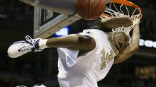 Georgia Tech's Jarrett Jack hangs onto the rim as he slams dunks late in the game in the Yellow Jackets' 57-54 win over Boston College in their second-round game of the NCAA tournament Sunday, March 21, 2004, in Milwaukee. (AP Photo/Morry Gash)