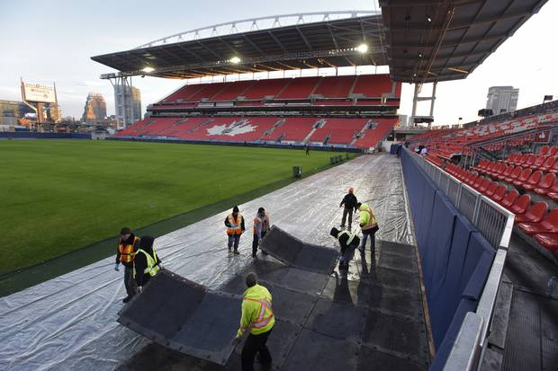 After the Grey Cup game, workers lay down mats in the end zone that will have stadium seats placed on top.