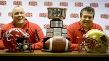 University of Calgary Dinos football coach Blake Nill, left, and Laval University Rouge et Or football coach Glen Constantin share a laugh with the Mitchell Bowl cup between them during a news conference in Calgary, Alta., Thursday, Nov. 17, 2011. The Rouge et Or will play the University of Calgary Dinos in the CIS Mitchell Bowl Friday evening.THE CANADIAN PRESS/Jeff McIntosh (Jeff McIntosh/THE CANADIAN PRESS)