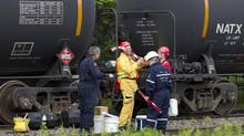 People from several juristictions – including the federal and Quebec environment ministries and the RCMP – prepare to do some investigative work in the area of nine tank cars sitting on the tracks in Nantes, Que., on July 11, 2013. (PETER POWER/THE GLOBE AND MAIL)