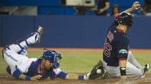 Toronto Blue Jays catcher J.P. Arencibia, left, is late with the tag as Boston Red Sox leftfielder Daniel Nava, right, slides safe at home plate to score a run during third inning AL baseball action in Toronto on Friday, June 1, 2012. (Nathan Denette/CP/Nathan Denette/CP)
