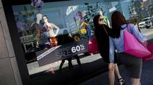 Shoppers pass the Holt Renfrew flagship store on Bloor Street in Toronto. (Moe Doiron/The Globe and Mail)