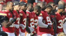 Kansas City Chiefs players stand arm-in-arm during a moment of silence before an NFL football game against the Carolina Panthers at Arrowhead Stadium in Kansas City, Mo., Sunday, Dec. 2, 2012. (Colin E. Braley/AP)