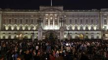People gather outside a floodlit Buckingham Palace in London to mark the birth of a baby boy to Prince William and Kate, Duchess of Cambridge, Monday, July 22, 2013. (Sang Tan/AP)