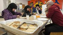From left: Ayesha Barakzai, 12, her sister Khadijah, 13, and their father sit with Lawrence Heights Middle School principal David Labelle while they enjoy a pancake breakfast hosted by the Toronto District School Board in Toronto on Dec. 25, 2013. (Jon Blacker for The Globe and Mail)