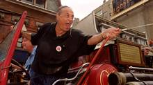 Toronto's Mayor Mel Lastman takes the fire hose to spectators as he rides down Yonge Street in an antique fire engine during the Gay Pride Parade in Toronto, Sunday June 25, 2000. (Tannis Toohey/CP)