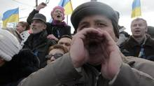Anti-government protestors rally in Kharkiv Sunday, just a few hundred metres away from opposing demonstrators who support closer ties with Russia. (Sergei Chuzavkov/AP)