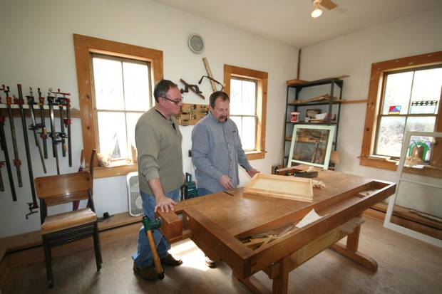Bill German, right, shows student Peter Corfield wooden storm windows.