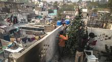 Boys of the Christian faith decorate a Christmas tree on the roof of their family home in Islamabad (ZOHRA BENSEMRA/REUTERS)
