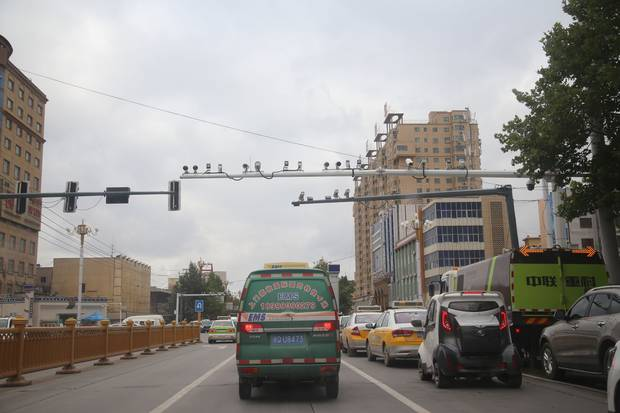 Surveillance cameras hang above the streets in Xinjiang. The government closely monitors where Xinjiang residents travel, how often they pray, what they wear and how they use the Internet.
