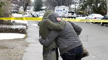Women cry and hug beside a makeshift memorial near the scene of the multiple fatal stabbings in northwest Calgary on Wednesday, April 16, 2014. (Larry MacDougal/The Canadian Press)