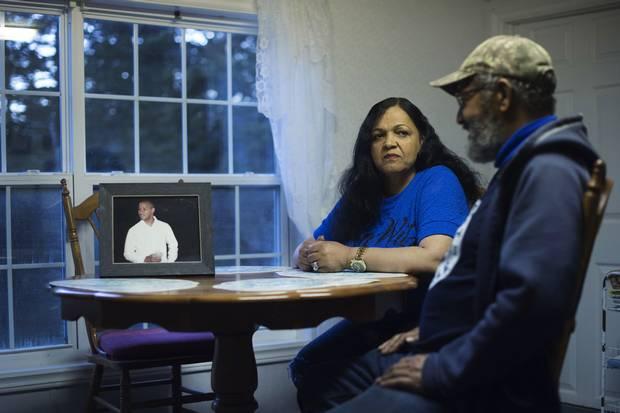 Lionel Desmond's half-aunt Sandra Greencorn and half-uncle Allan Desmond sit beside a photo of Lionel.