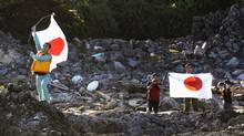 Members of a Japanese nationalist group raise Japanese flags as they land on Uotsuri island, part of the disputed islands in the East China Sea, known as the Senkaku isles in Japan and Diaoyu islands in China, in this photo by Kyodo August 19, 2012. (KYODO/REUTERS)