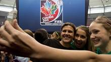Team Canada's Christine Sinclair takes a photo with young soccer fans as FIFA unveils the official emblem for the 2015 Women's World Cup soccer tournament during a ceremony in downtown Vancouver, B.C. Friday, December, 14, 2012. (Jonathan Hayward/THE CANADIAN PRESS)
