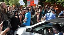 Protesters surround a car trying to drive through them as they try to disrupt the opening gala at the Canadian Grand Prix in Montreal on Thursday, June 7, 2012. (Tom Boland/Canadian Press)
