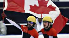 Canada's Charles Hamelin, left, celebrates his gold medal with teammate and silver medallist Michael Gilday in the the men's 1000-metre final at the ISU Korean Air World Cup short track speed skating Sunday, October 30, 2011 in Saguenay Que. THE CANADIAN PRESS/Jacques Boissinot (Jacques Boissinot/CP)