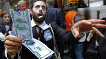 "A demonstrator holds play money while dressed as a ""corporate zombie"" as he walks with others taking part in an Occupy Wall Street protest in lower Manhattan in New York, October 3, 2011. The Occupy Wall Street protests moved into their third week Monday with demonstrators camping out in Zuccotti Park. (Mike Segar/Reuters/Mike Segar/Reuters)"