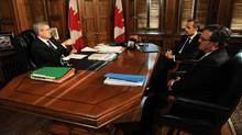 Prime Minister Stephen Harper speaks with Finance Minister Jim Flaherty and Bank of Canada Governor Mark Carney during a meeting in his office on Parliament Hill in Ottawa on Tuesday, September 27, 2011. (Sean Kilpatrick/THE CANADIAN PRESS)