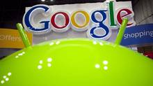 In this Jan. 17, 2012 photo, a sign for Google is displayed behind the Google android robot, at the National Retail Federation, in New York. (Mark Lennihan/Mark Lennihan/AP)
