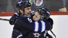 Winnipeg Jets' Alexander Burmistrov, right, celebrates his goal against the Boston Bruins' with teammate Mark Stuart during the second period of their NHL hockey game in Winnipeg on Friday. (FRED GREENSLADE)
