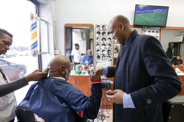 Mr. Hussen chats with Milton Esson while he gets his hair cut.