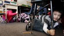 Joseph Kim takes cover under his desk during an earthquake drill at Hollyburn Elementary School in West Vancouver, B.C., on Wednesday January 26, 2011. (Darryl Dyck/ The Canadian Press/Darryl Dyck/ The Canadian Press)