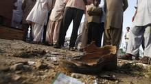 Men look at a tattered shoe at the site of Tuesday's bomb blast, outside the campaign office of the Muttahida Qaumi Movement (MQM) political party, in Karachi April 24, 2013. At least five people were killed and 15 others injured on Tuesday night after militants set off a bomb targeting a roadside election camp of the MQM in Karachi, according to local media. (Athar Hussain/Reuters)