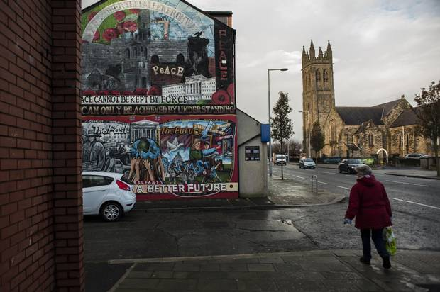 A local woman walks by a loyalist mural in Newtownards Road, a predominately protestant and loyalist neighbourhood in East Belfast, Northern Ireland.