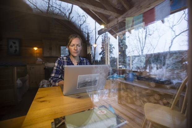 Crystal Schick/Freelance Kate Harris, author of Lands of Lost Borders, works on her computer at her little workstation in her one-room log cabin outside Atlin, B.C. on Jan. 20, 2018.