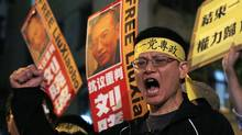 Pro-democracy protesters hold the picture of Chinese dissident Liu Xiaobo during a demonstration outside the China's Liaison Office in Hong Kong Friday, Oct. 8, 2010. Imprisoned Chinese dissident Liu Xiaobo won the 2010 Nobel Peace Prize on Friday for using non-violence to demand fundamental human rights in his homeland. (Kin Cheung/Kin Cheung/AP)