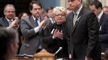 Quebec Public Security Minister Stephane Bergeron, right, is applauded by members of the legislature after making a statement on the anniversary of the Polytechnic shooting and the firearm registry, Thursday, December 6, 2012, at the legislature in Quebec City. (Jacques Boissinot/THE CANADIAN PRESS)