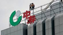 Labourers fix the logo of China Life Insurance, the top Chinese insurer, in Xiangfan, central China's Hubei province. (© STR New / Reuters)