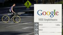 A bicyclist crosses the street next to Google Inc. signage displayed company headquarters in Mountain View, California, U.S., on Thursday, Oct. 13, 2011. (Tony Avelar/Bloomberg)