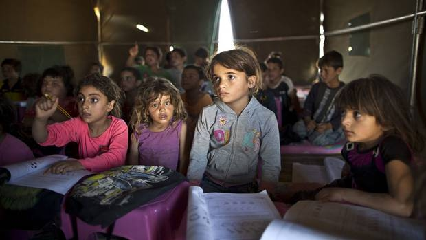 Syrian refugee children attend a class at a makeshift school set up in a tent at an informal settlement near the Syrian border on the outskirts of Mafraq, Jordan on Aug. 11, 2015. Forty percent of children from five conflict-scarred Middle Eastern countries are not in school, the U.N. child welfare agency said in a report Thursday, Sept. 3, 2015, warning of a lost generation and a dim future for the region.