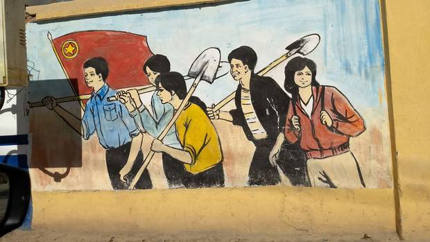 A wall painting in Xinjiang shows Uyghurs working happily under the Chinese flag.