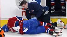 Montreal Canadiens defenseman Alexei Emelin is helped by a trainer after being checked by Boston Bruins left wing Milan Lucic, not shown, during first period National Hockey League action Saturday, April 6, 2013 in Montreal (The Canadian Press)