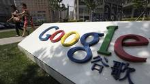 Women walk past the logo of Google in front of its former headquarters, in Beijing June 2, 2011. Suspected Chinese hackers tried to steal the passwords of hundreds of Google email account holders, including those of senior U.S. government officials, Chinese activists and journalists, the Internet company said. (JASON LEE/REUTERS)