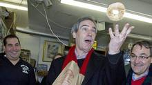 Liberal Leader Michael Ignatieff flips a bagel into the air during a campaign stop in a Montreal with former cabinet minister Martin Cauchon on March 27, 2011. (CHRISTINNE MUSCHI/REUTERS)