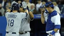 Tampa Bay Rays batter Ben Zobrist celebrates his two-run home run with Desmond Jennings (C) in front of Toronto Blue Jays catcher Jeff Mathis (R) during the first inning of their MLB American League baseball game in Toronto April 18, 2012. (MIKE CASSESE/REUTERS)