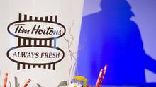 The shadow of Paul House, chief executive of Tim Hortons, is cast on the wall as he speaks at the iconic coffee chain's AGM in Toronto on May 10, 2012. (Chris Young/The Canadian Press)