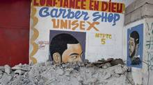 "A sign for a barber shop that reads ""confidence in God"" is still buried in rubble Tuesday, January 11, 2011 in Port-au-Prince on the eve of the first anniversary of the earthquake that killed more than 200,000 people and displaced some 1.5 million more. (Paul Chiasson/THE CANADIAN PRESS)"