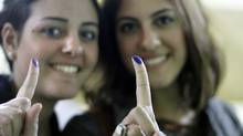 Young women show their inked fingers after voting in an election that Egyptians hope will usher in a democratic age after decades of dictatorship. (Amr Nabil/Amr Nabil/AP)