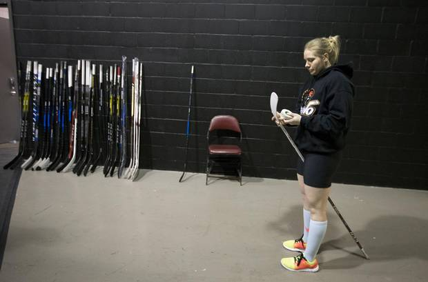 Haley Irwin of the Calgary Inferno, tapes up her hockey stick prior to their Canadian Women's Hockey League (CWHL) game against Les Canadiennes at the Bell Center in Montreal, Dec. 10, 2016.