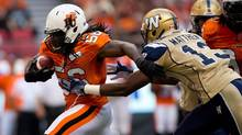 B.C. Lions' Solomon Elimimian, left, carries the ball after intercepting a Winnipeg Blue Bombers pass as Chris Matthews, right, gives chase during the first half of a CFL football game in Vancouver, B.C., on Monday August 5, 2013. (DARRYL DYCK/THE CANADIAN PRESS)